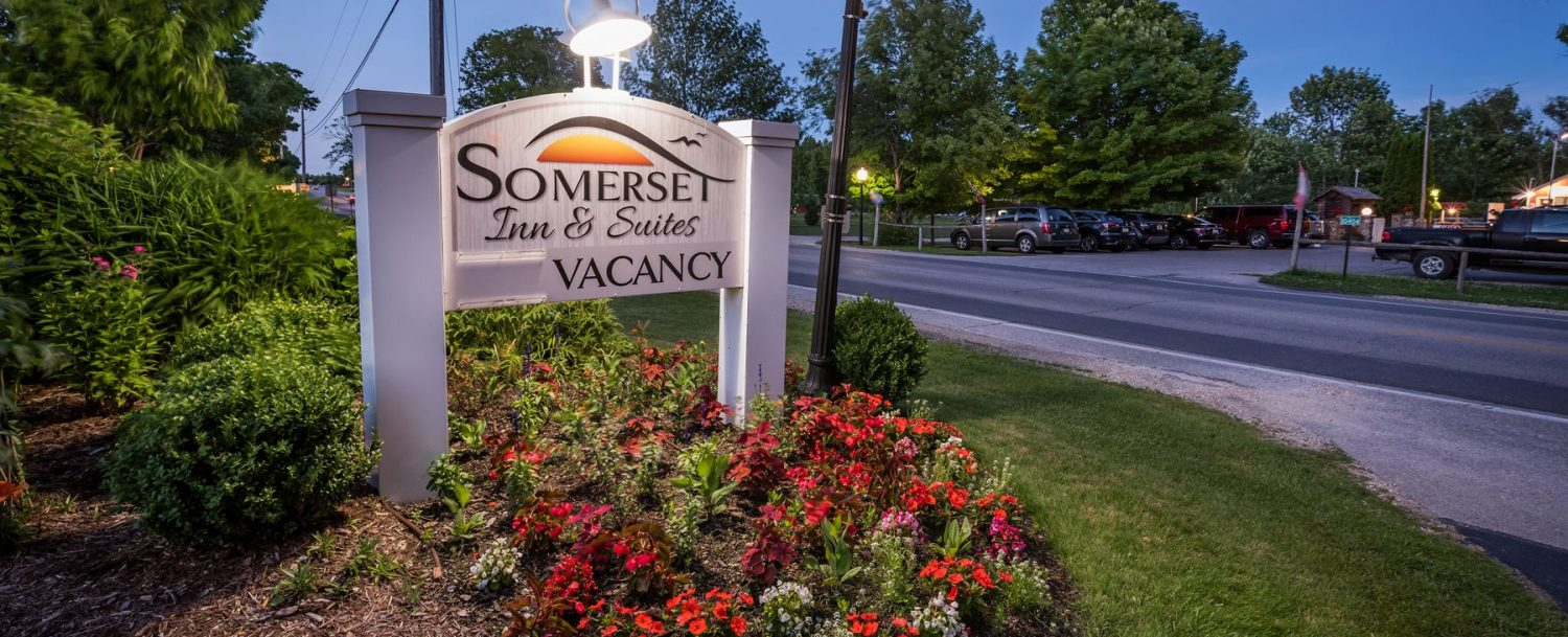Somerset Inn & Suites sign at dusk lit up with red flowers surrounding it